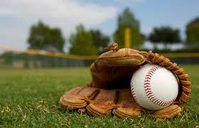 A baseball in a glove on the grass